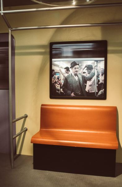 Sala que reproduz vagão de metrô, com fotos de Adoniran nas janelas