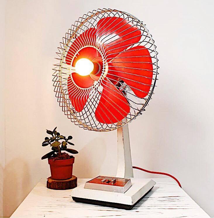 Ventilador de mesa com hastes vermelhas e uma luz no meio