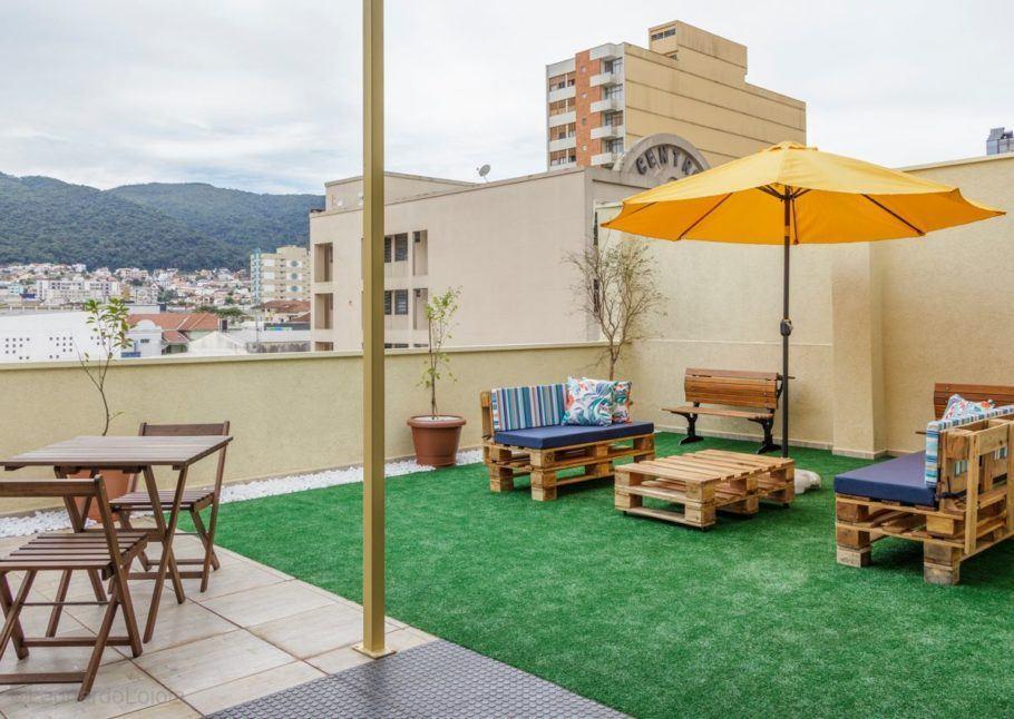 Área de convivência a céu aberto com mesas e bancos feitos de pallet