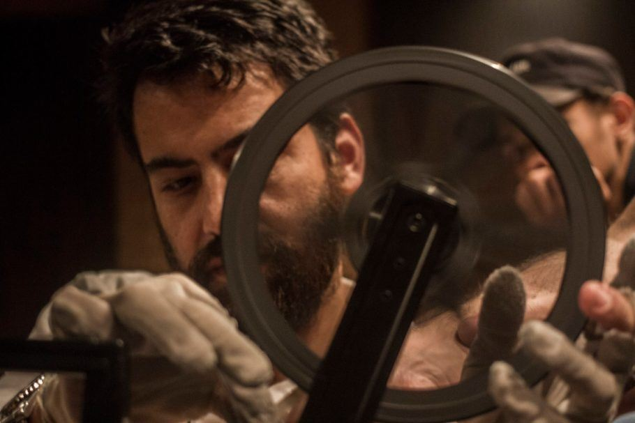 Homem colocando filme no projetor de super 8