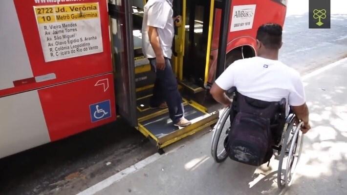 Cadeirante é auxiliado por motorista a subir no ônibus em São Paulo