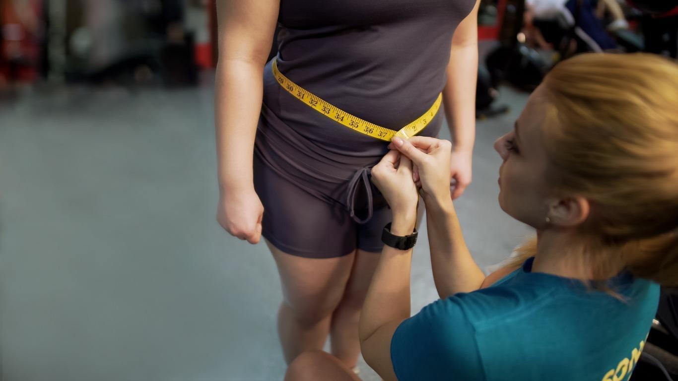 personal trainer medindo cirfunferência da barriga de uma mulher