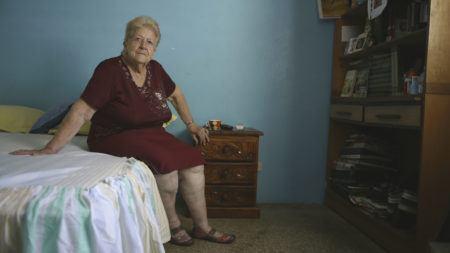"""Foto do filme """"Mulheres do Caos Venezuelano"""", com uma senhora sentada em uma cama"""