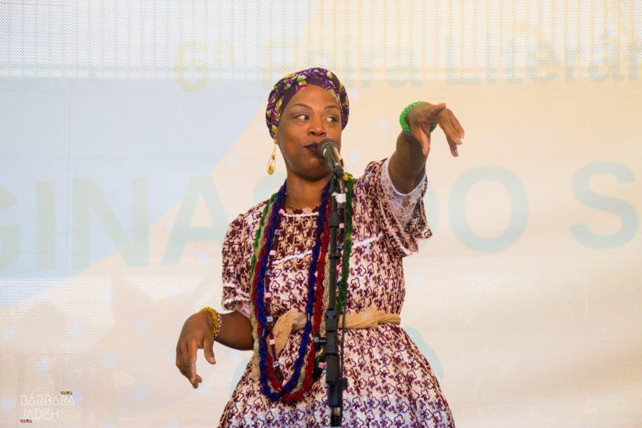 Foto da Nega Duda cantando com um vestido estampado, colares e turbante
