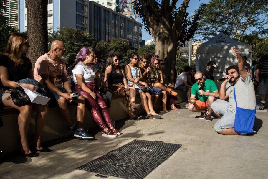 Poetas Ambulantes se apresentam para pessoas sentadas na avenida Paulista