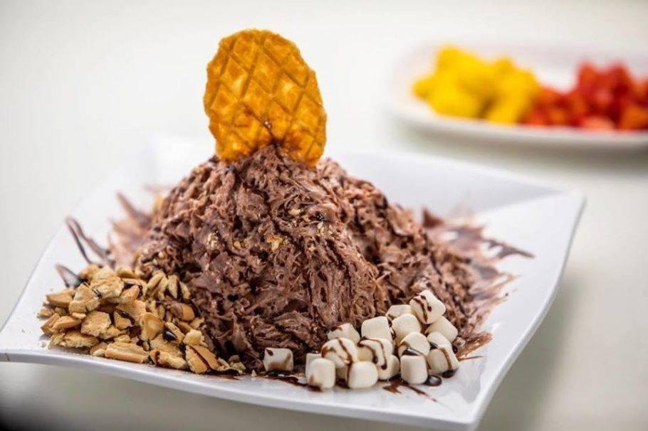 Raspadinha de neve de chocolate com mini-marshmallows, biscoito maizena triturado, cobertura de chocolate com uma bolacha belga para finalizar