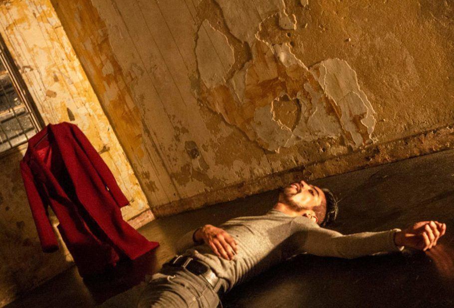 """Foto do espetáculo """"Sardónico"""", em que um dançarino está deitado no chão com uma mão no peito"""