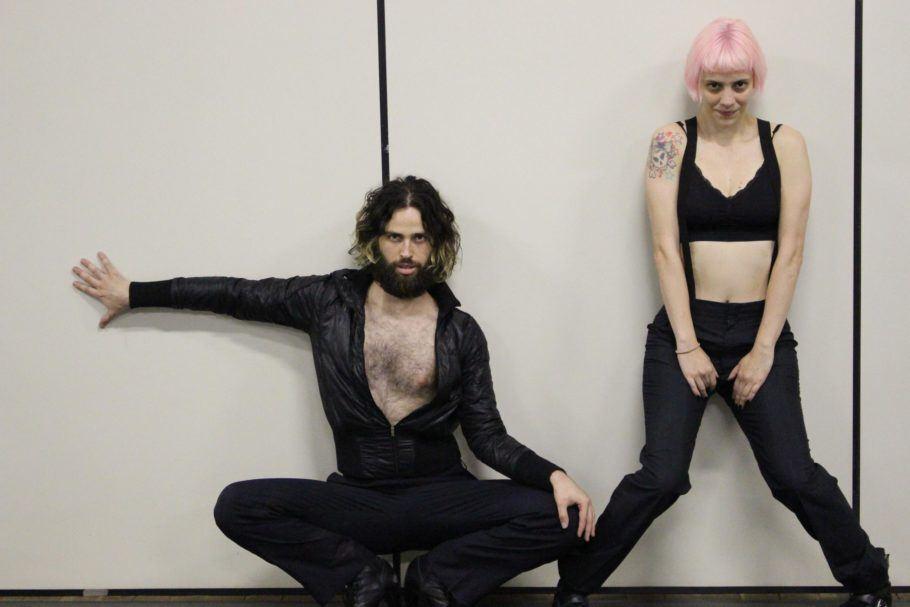 """Foto do espetáculo """"Satisfação do Cliente"""", em que dois dençarinos vestindo roupas pretas estão encostados na parede olhando para a câmera"""
