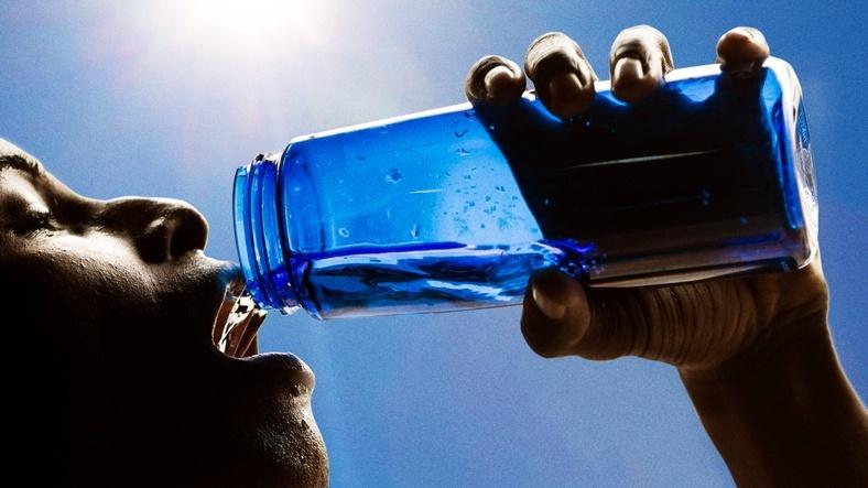pessoa bebendo água na garrafa
