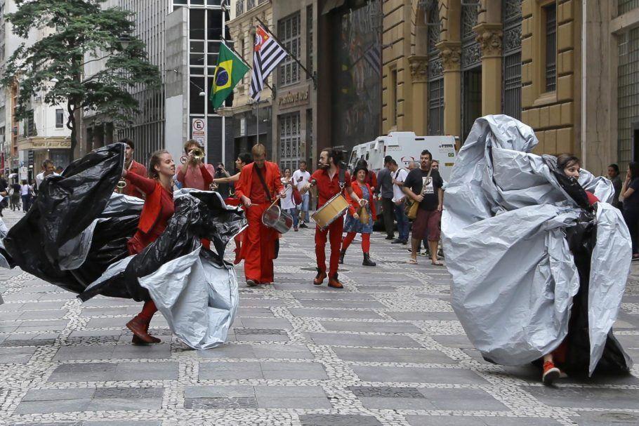 """Foto do espetáculo """"Solos de Rua"""", em que duas dançarinas envoltas em capas preto e brancas andam pelo centro de São Paulo acompanhadas por percussionistas"""