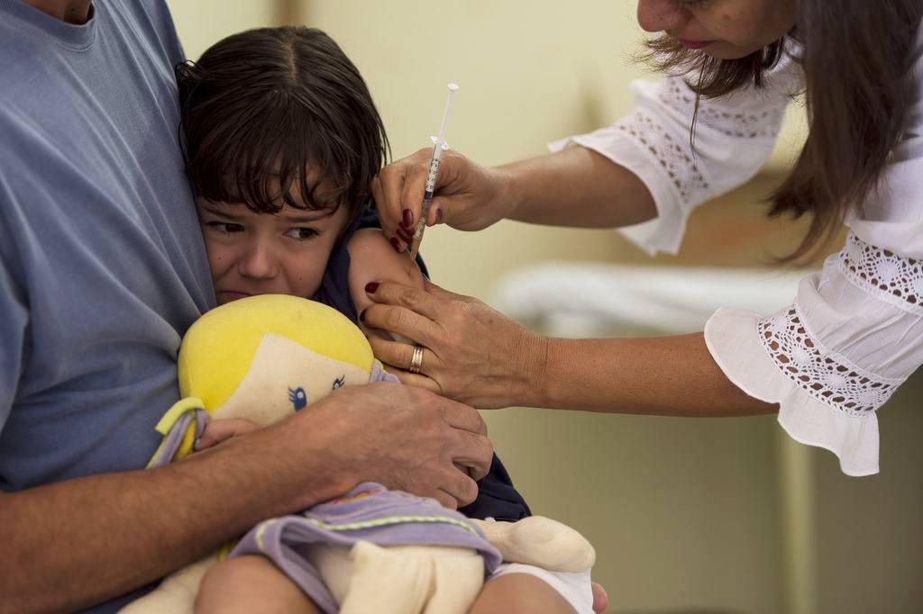 criança tomando vacina com boneca na mão