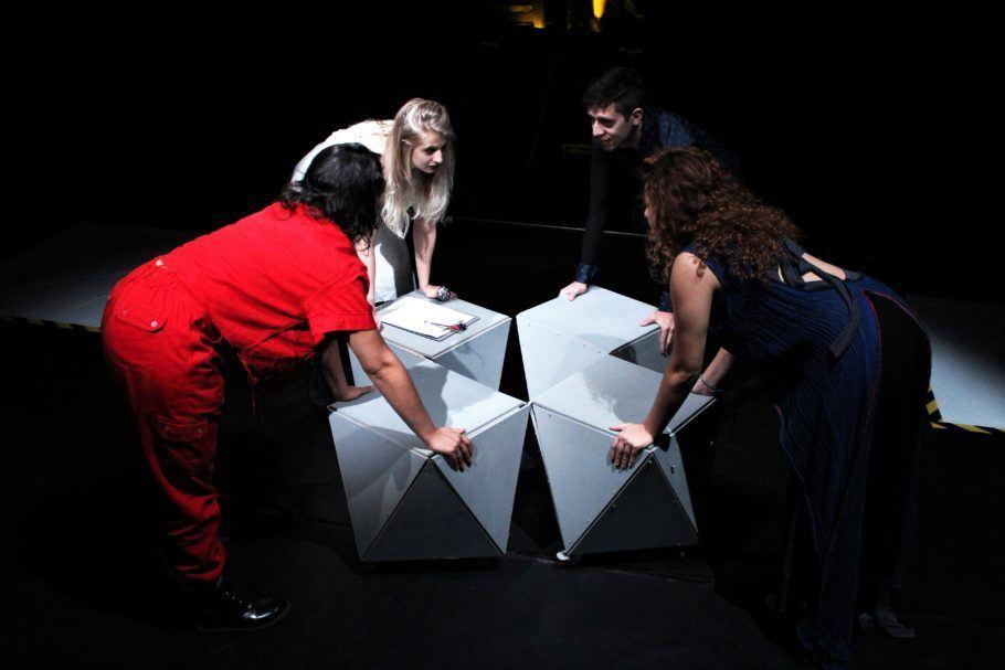 3 atrizes e 1 ator em rola no palco segurando mesinhas brancas