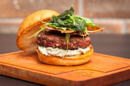 O Saltim Burger é uma das sensações da Check-In, com burger bovino, sálvia frita, pesto de alcachofra, rúcula com azeite, limão siciliano e Parma Crocante