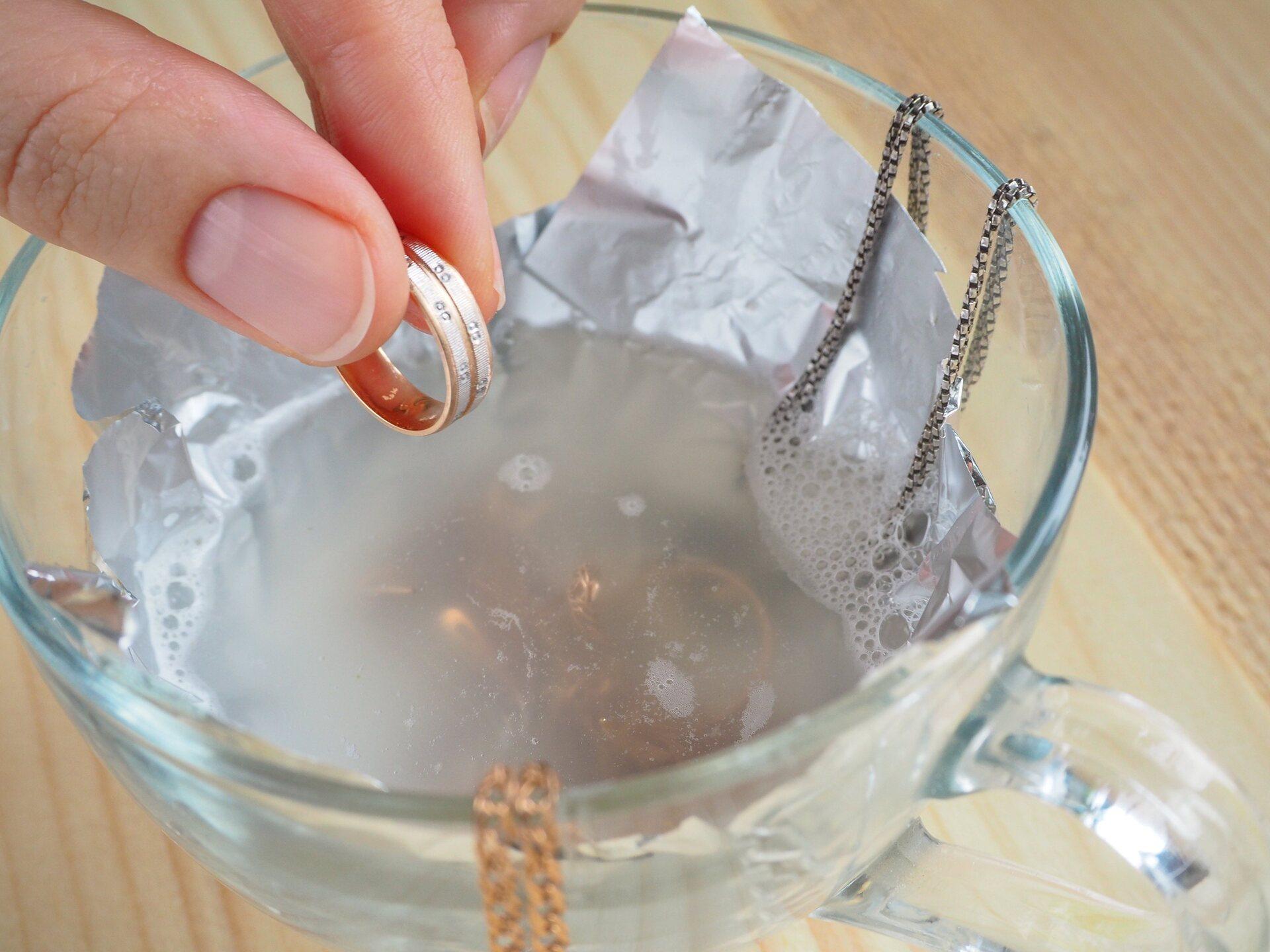 Xícara com água e papel alumínio para clarear alianças de prata