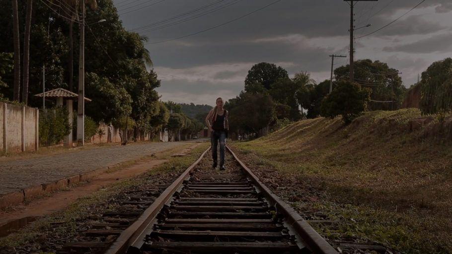 """Foto do curta """"Depois da Cuva"""", em que uma mulher anda sobre uma linha de trem em um dia cinza"""