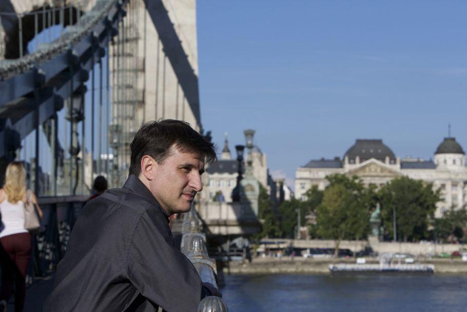 """Foto do curta """"Diário De Um Compositor Em Viagem"""" em que um homem está reflexivo em meio a uma cidade"""