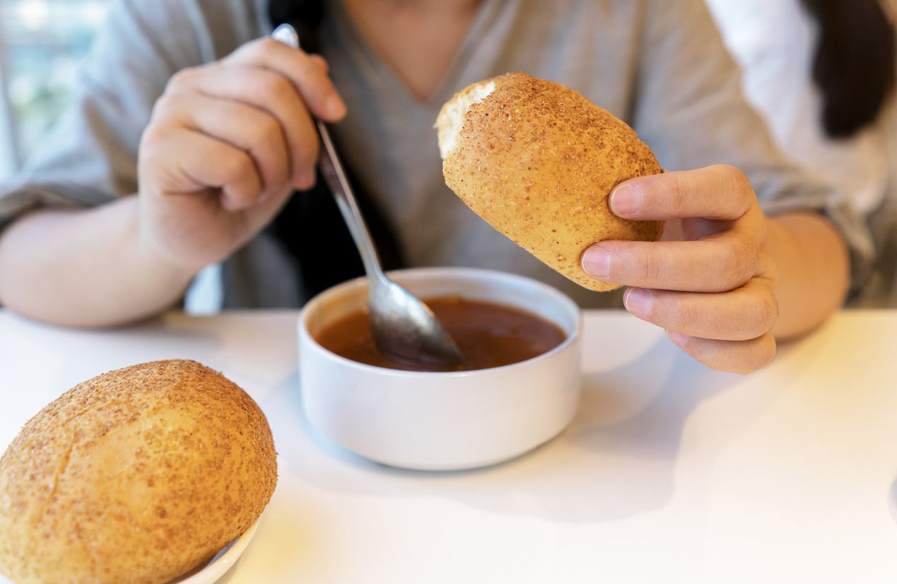 menina comendo pão com sopa