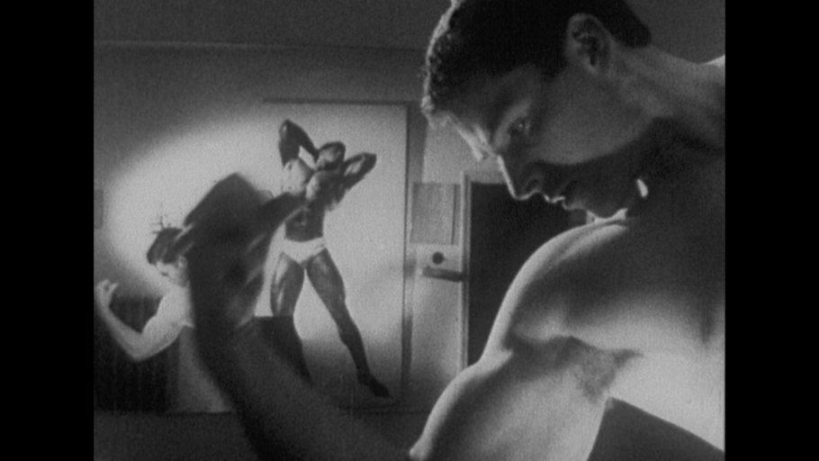 """Foto em preto e branco do curta """"Hércules"""", em que um homem está admirando seus músculos"""