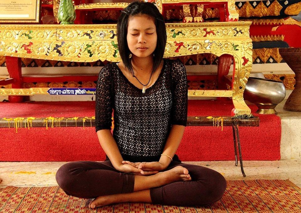 mulher sentada em um templo meditando