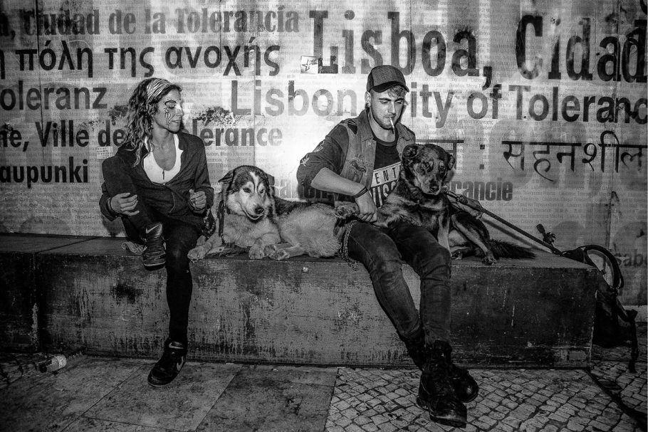 Foto em preto e branco de dois de moradores de rua e seus cães