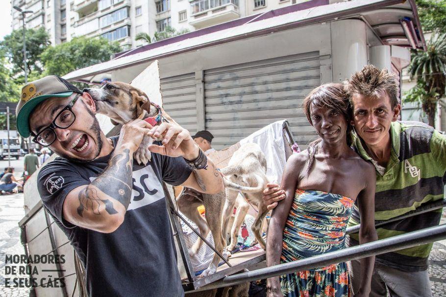 Três moradores de rua e um cachorro dentro de um carrinho se mercado