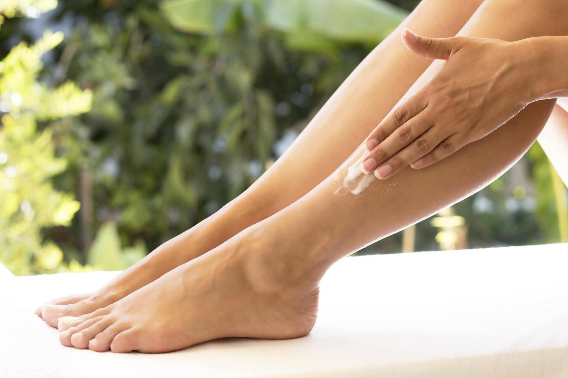 Mulher passando hidratante na perna