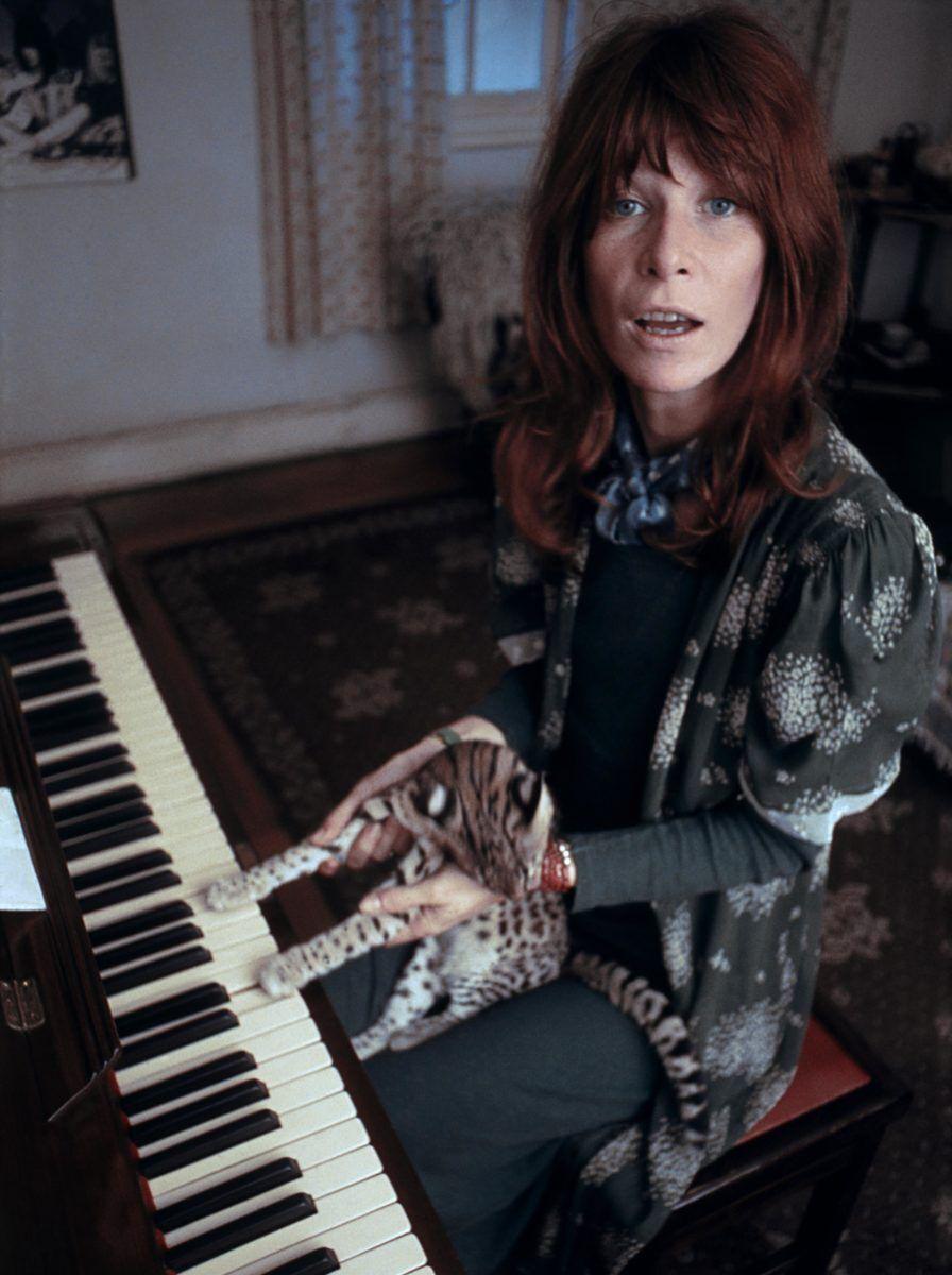 Foto colorida da Rita Lee no teclado com um gato no colo