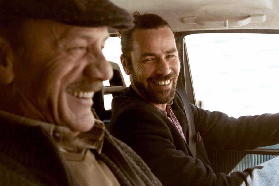 """Cena do filme """"Wajib - Um Convite de Casamento"""", com um pai e um filho sorrindo em um carro"""