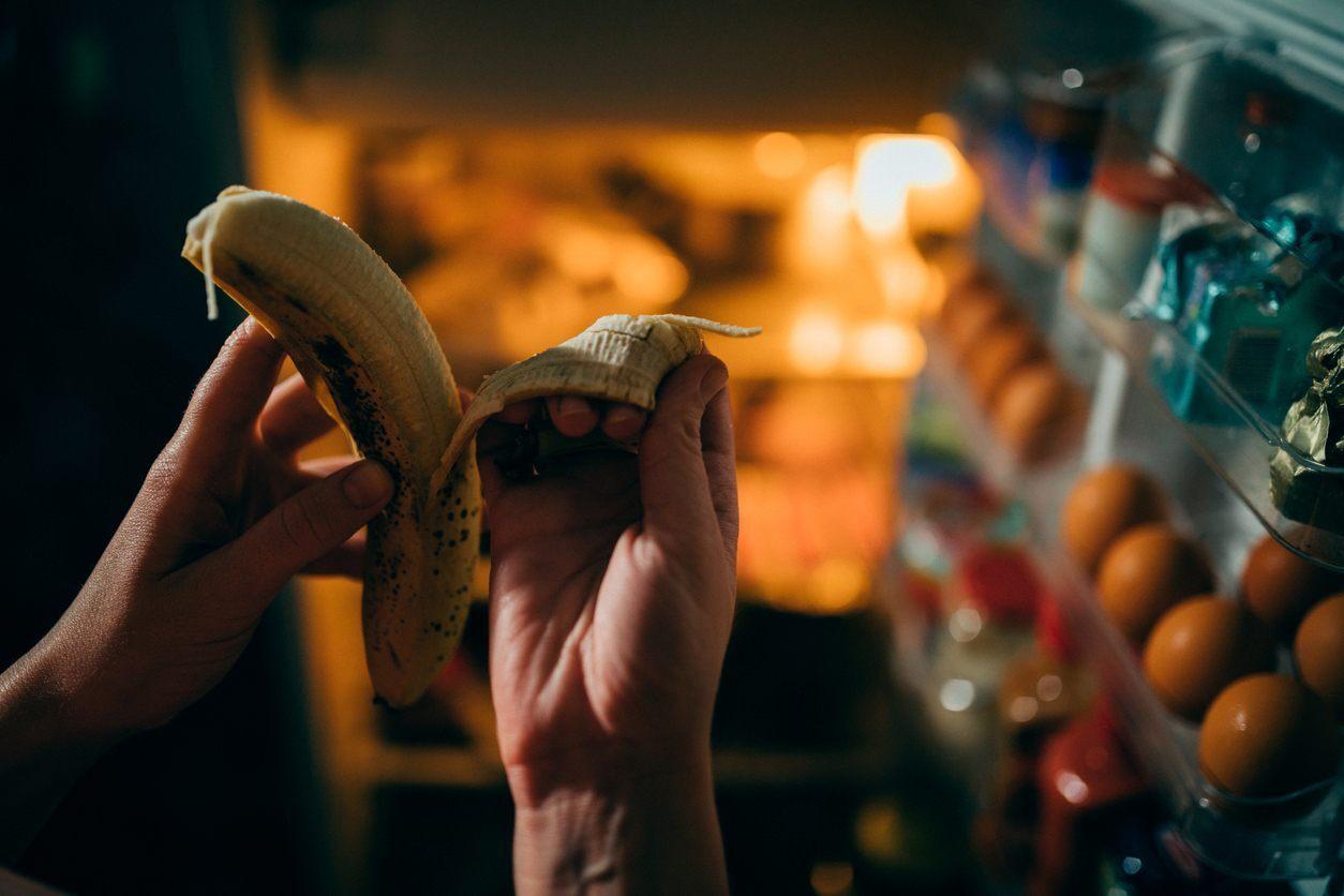 mulher comendo uma banana com a geladeira aberta