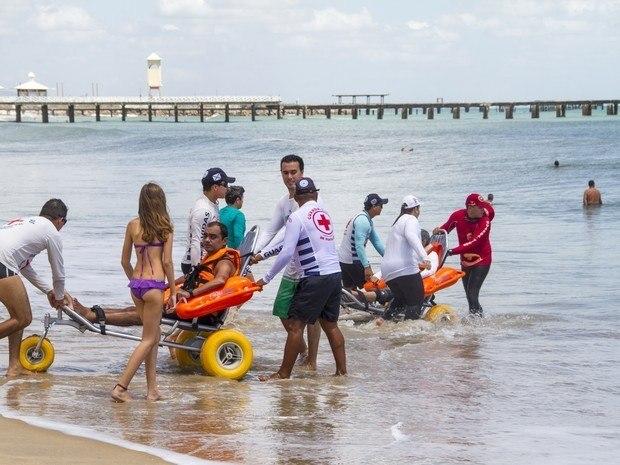cadeirantes entrando no mar com cadeira anfíbia