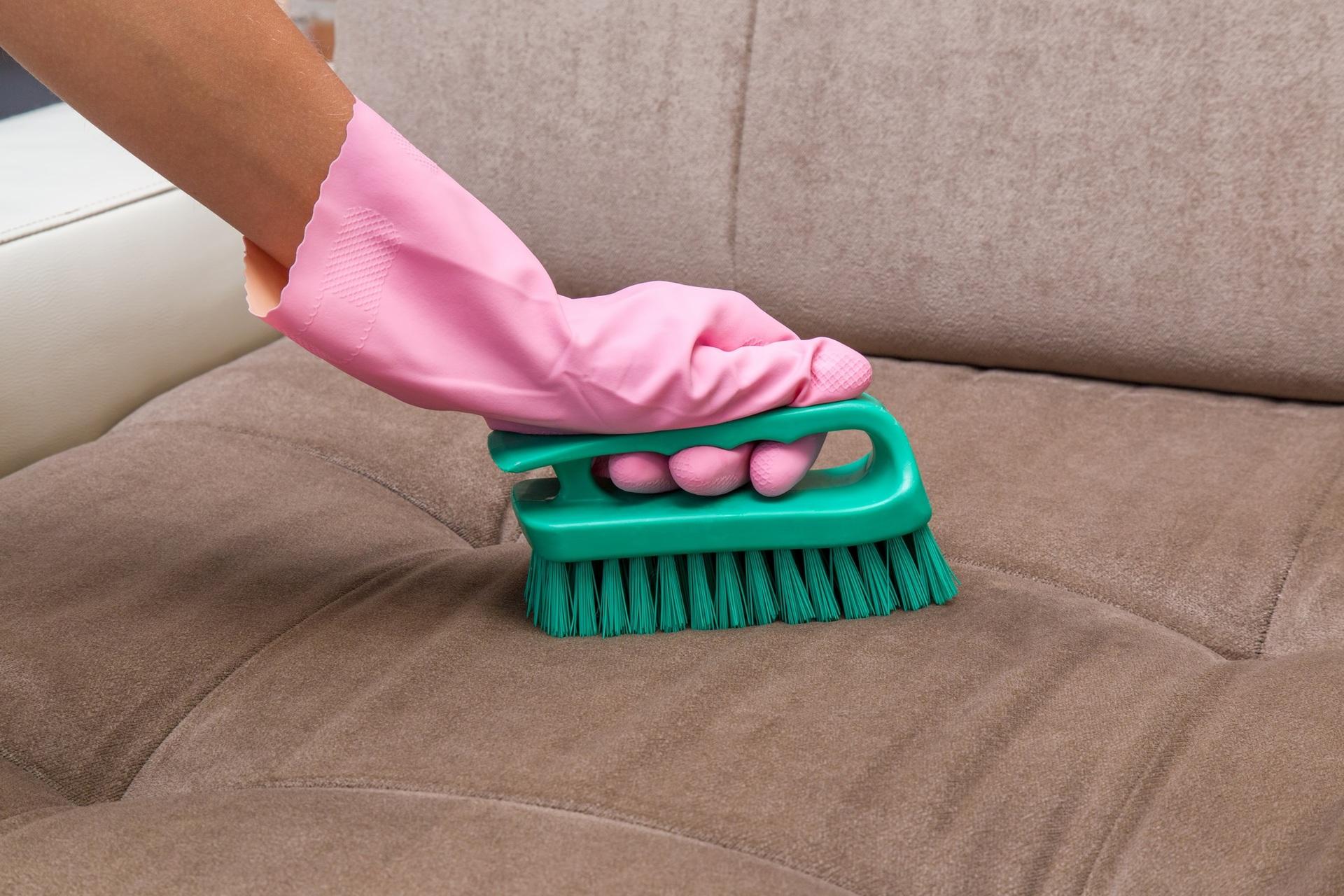 Pessoa limpando sofá com escova