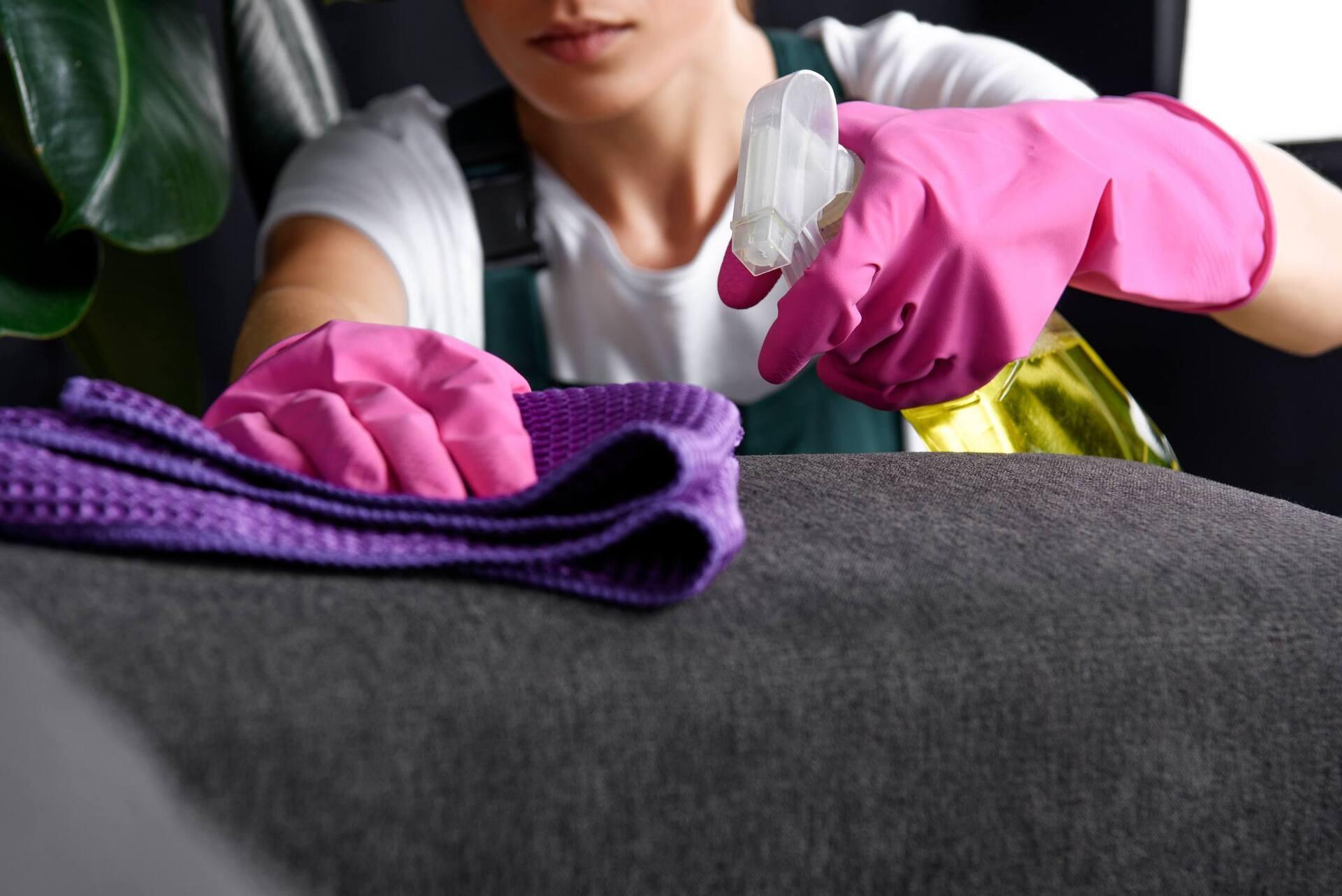 Mulher com borrifador e pano limpando sofá