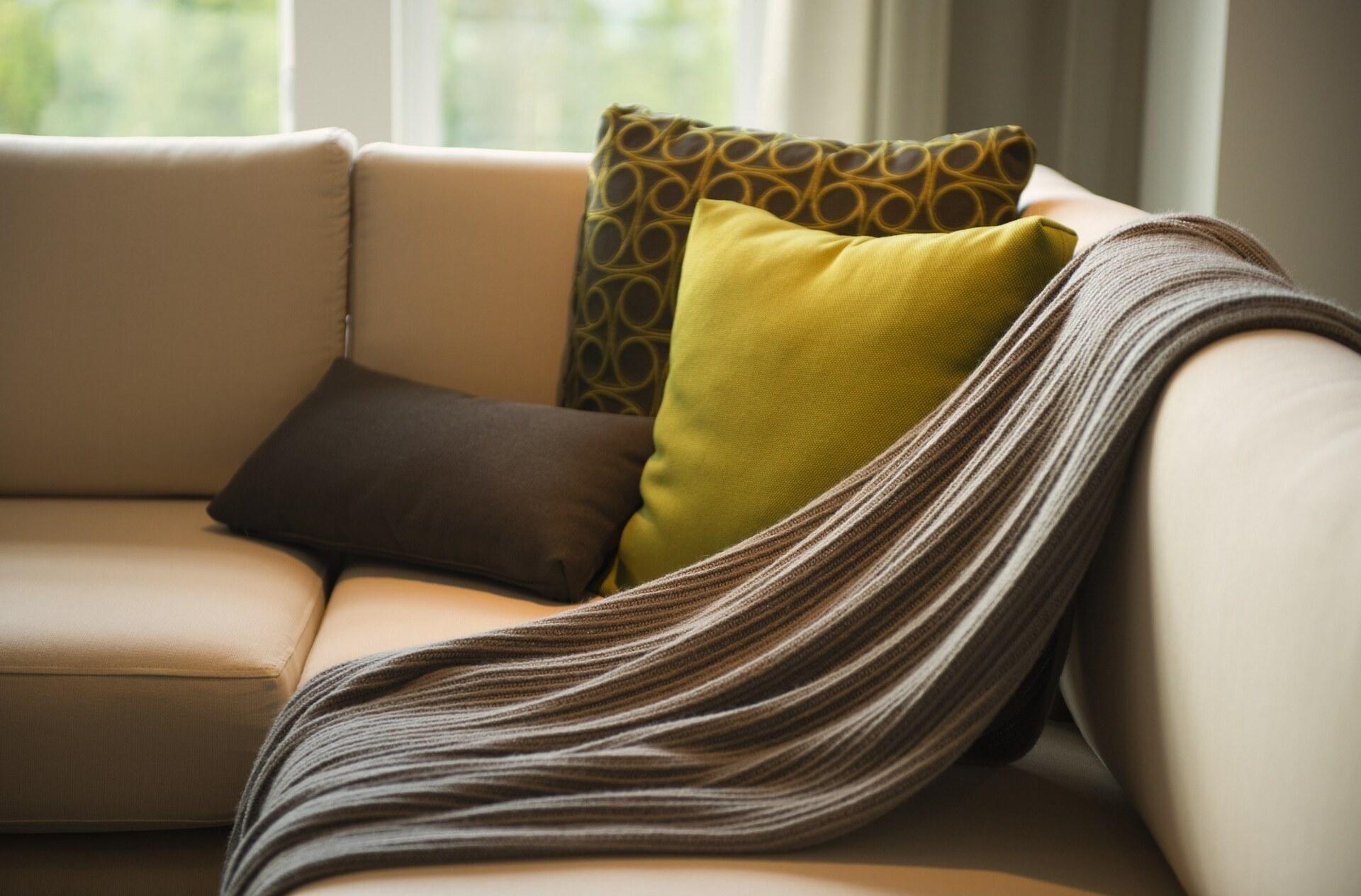 Sofá com manta e almofadas
