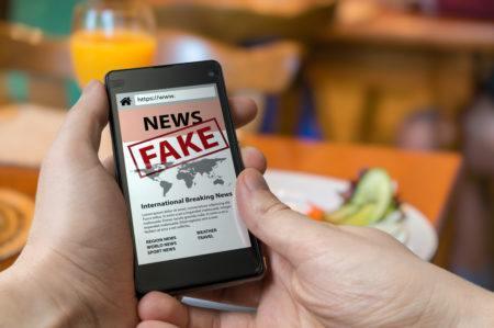 homem segurando um celular com a palavra fake news na tela