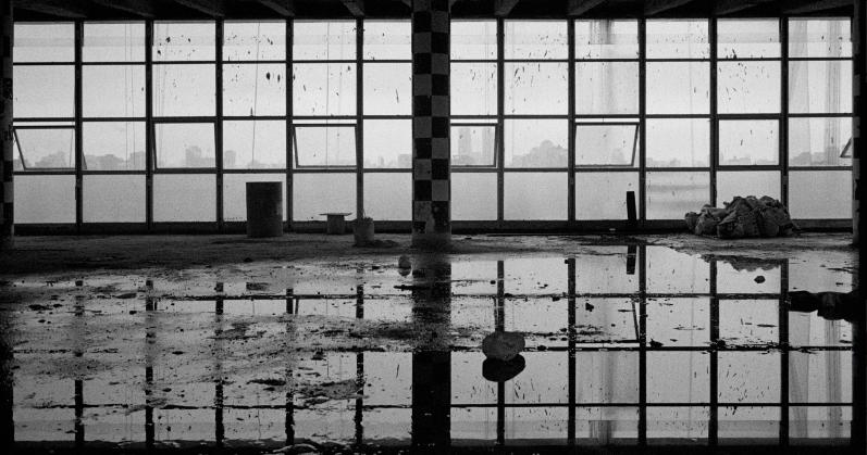 Foto em preto e btanco mostrando uma janela de vidro e uma grande poça de água do lado de fora