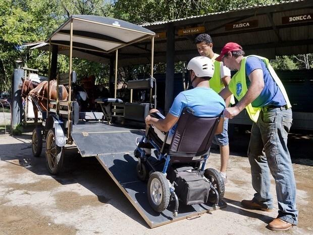 cadeirante sendo transportado em um carrinho de turismo