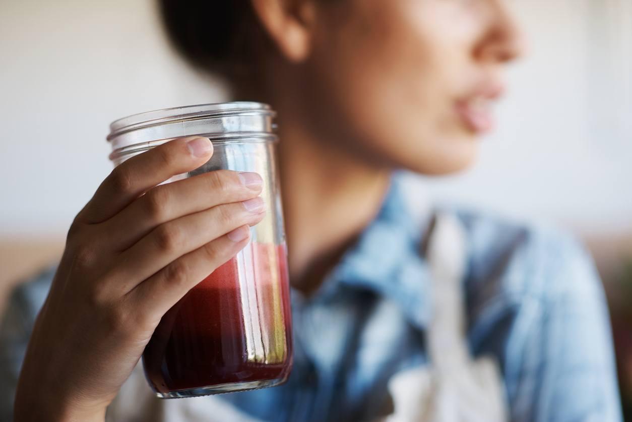 mulher segurando um copo de suco