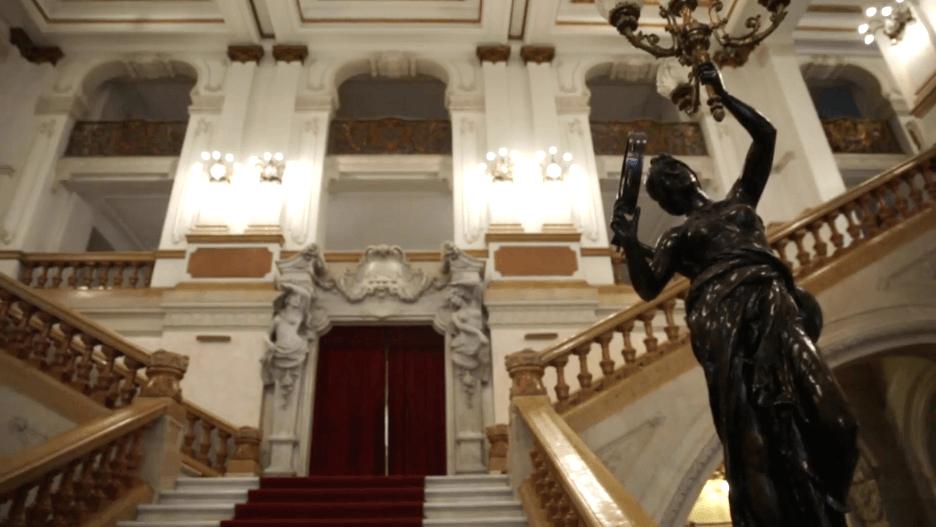 Vista do hall de entrada do Theatro Municipal de São Paulo com obras de arte e escadarias deslumbrantes