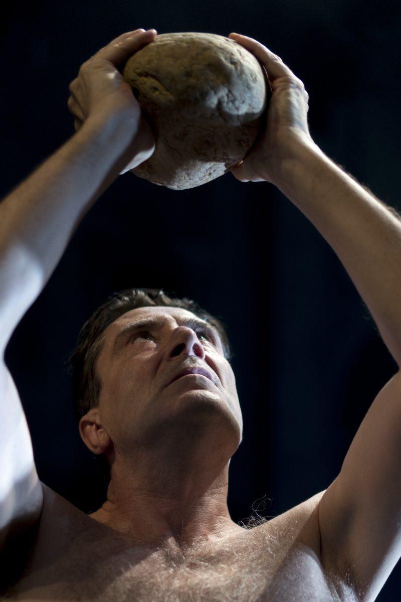 Close de ator segurando um coco com as mãos para cima