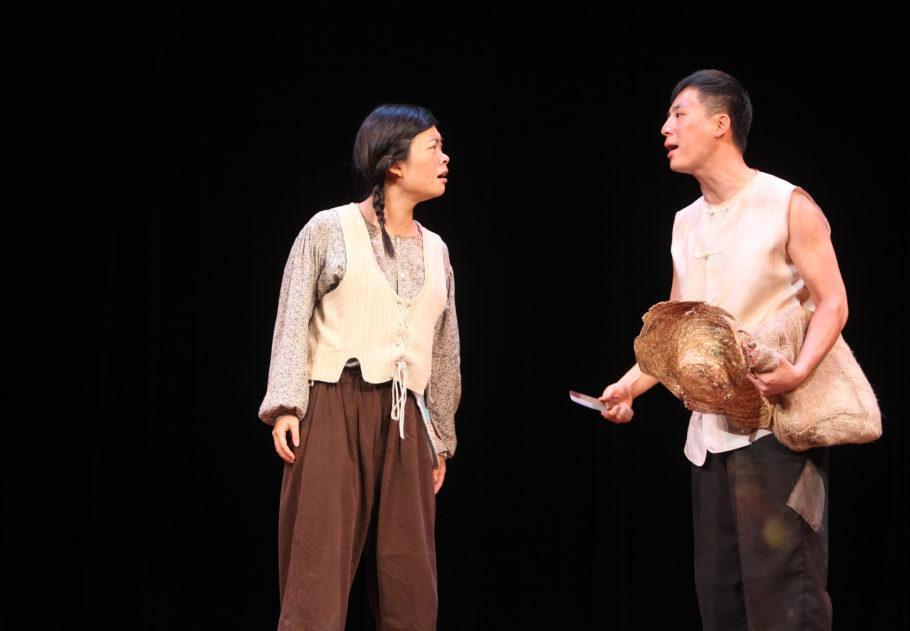 Um ator e uma atriz em cena em um fundo preto