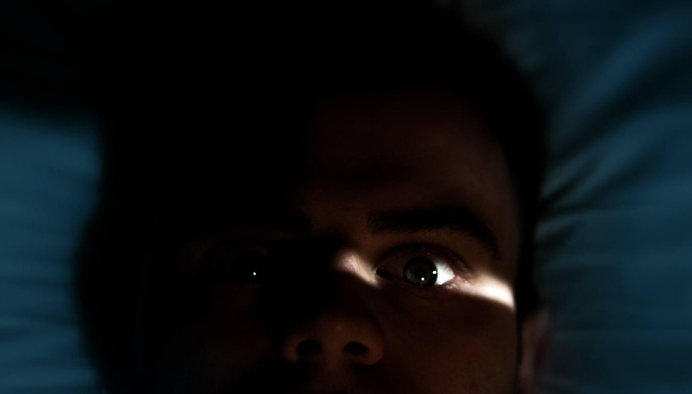 homem na cama com cara de medo
