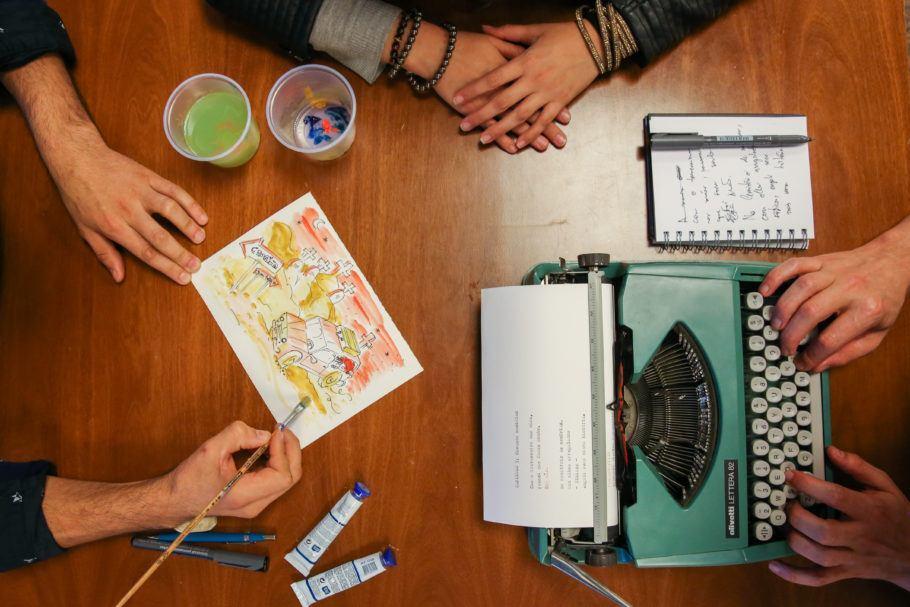 3 pessoas sentadas em uma mesa: uma na máquina de escrever, uma pintando um cartão-postal e outra com as mãos em cima da mesa