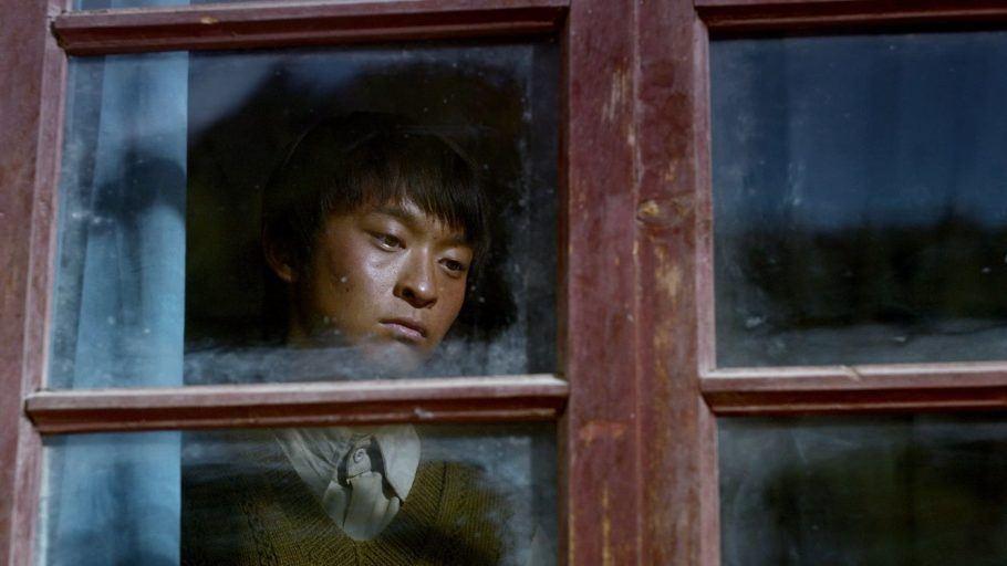 Um menino encostado em uma janela