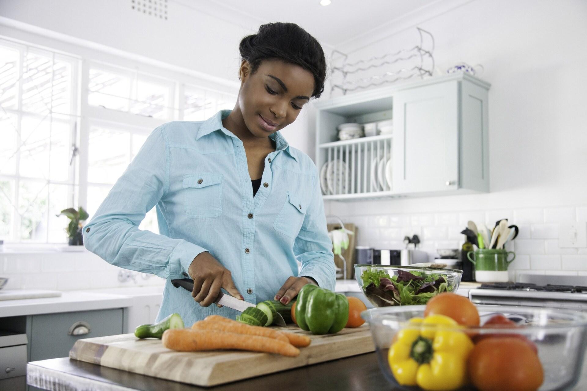 Mulher cozinhando com alimentos saudáveis