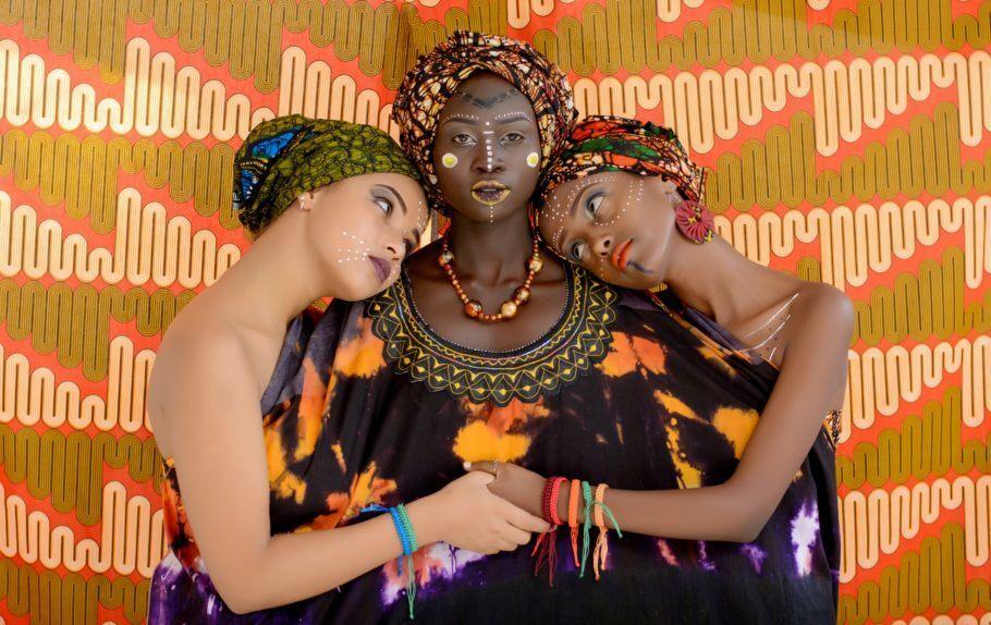 Três mulheres com trajes típicos africanos abraçadas
