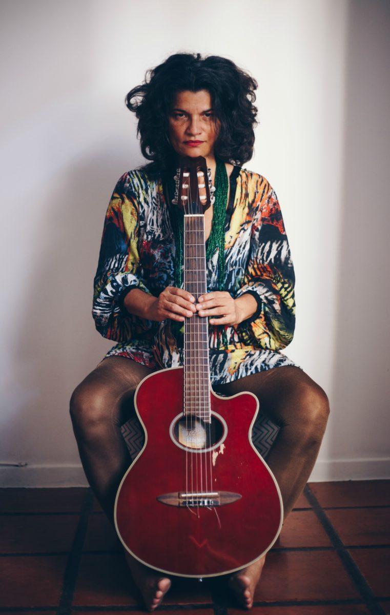 Foto de Déa Trancoso sentada segurando um violão vermelho