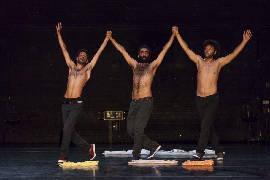 """Espetáculo """"Displacement"""", de Mithkal Alzghair, com três bailarinos em cena de mãos dadas e levantadas para o ar"""