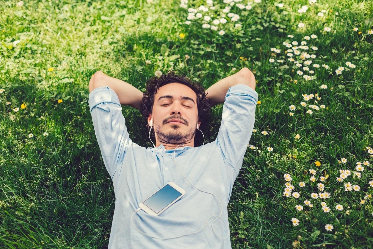 homem deitado na grama com o fone de ouvido conectado no celular