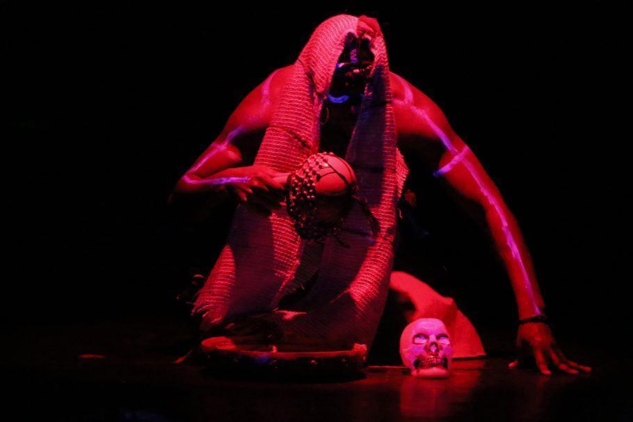 Ator em cena agachado, com uma luz vermelha incidindo sobre ele