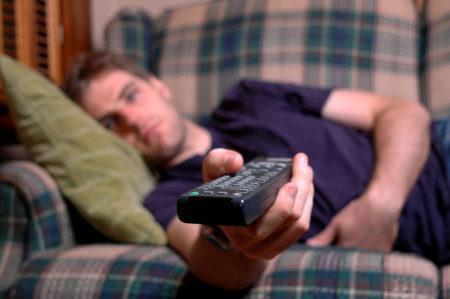 homem deitado no sofá com controle remoto na mão